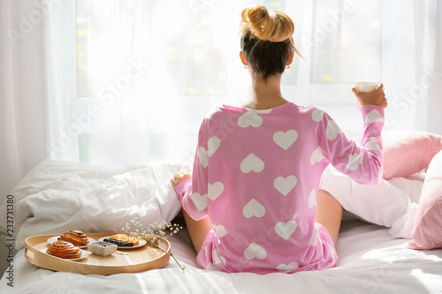 Obraz na plátně Young woman having delicious breakfast on bed