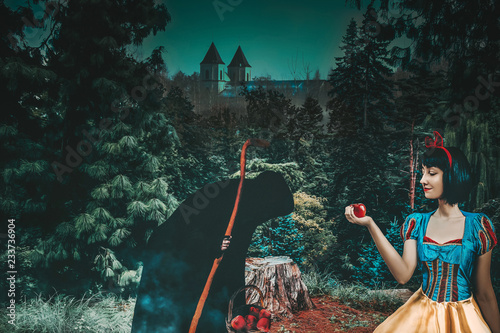 Fotografie, Obraz  Snow White girl with old evil witch gives her an apple in the mysterious forest closeup