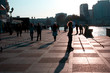 People walk along the promenade in the sea city at sunset. Citizens rest, rollerblading on the embankment in the rays of the setting sun.
