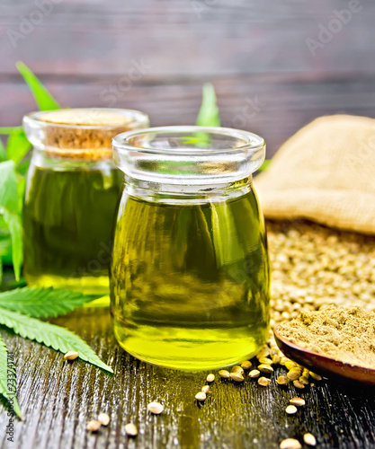 Foto op Plexiglas Kruiderij Oil hemp in two jars and flour in spoon on wooden board