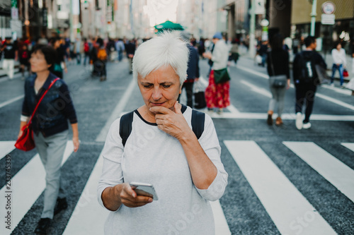 Fotografía  .Caucasian middle-aged woman traveling through Japan. Touring the city of Tokyo