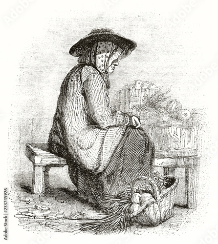 Old illustration of a Normand peasant seated close to a basket vegetables filled in traditional costume Canvas Print