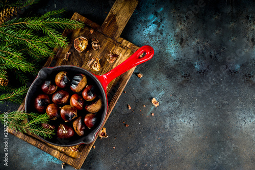 Fototapeta Cracked roasted chestnuts, traditional autumn winter homemade snack, on small chestnut's frying pan, copy space obraz