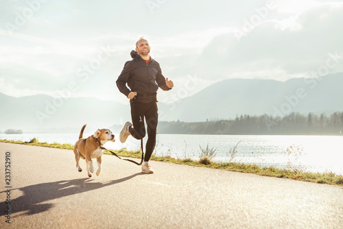 Obraz na plátně  Morning jogging with pet: man runs together with his beagle dog