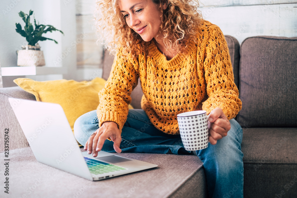Fototapeta Nice beautiful lady with blonde curly hair work at the notebook sit down on the sofa at home - check on oline shops for cyber monday sales - technology woman concept for alternative office freelance