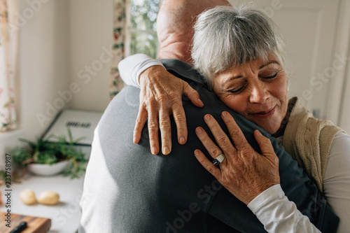 Senior couple hugging each other at home Wallpaper Mural