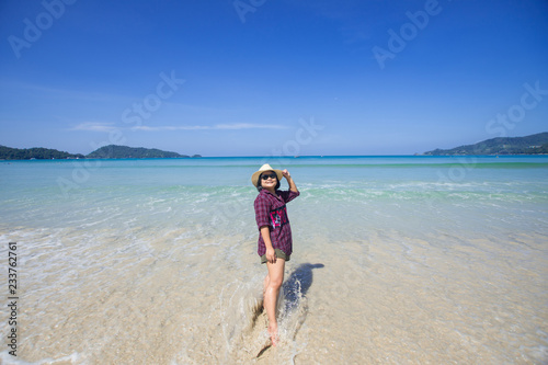 happy travel woman stand on sand of the sea with blue sky at sunny day. subject is blurred.
