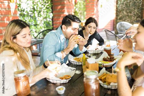 Fototapeta Men And Women Having Midday Meal At Burger Shop obraz