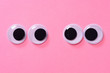 Googly eyes of pair of lovers on rose background. Close up.