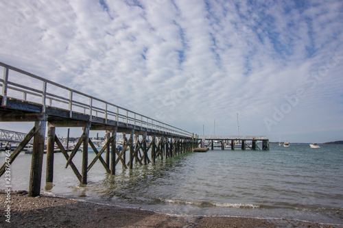 pier at low tide with choppy, cloudy sky