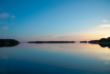 The Beautifully Reflected Pastel Hues Of Sunset A Few Days After Midsummer, Viewed Through A Backdrop Of Trees And Clouds In A Cove On The Island Of Nicklösa In The Åland Islands, Finland.
