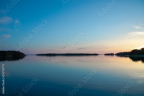 The beautifully reflected pastel hues of sunset a few days after midsummer, viewed through a backdrop of trees and clouds in a cove on the Island of Nicklösa in the Åland Islands, Finland Canvas Print