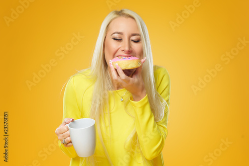 Woman holding colorful donut with sprinkles on a yellow background. Cup of coffee. Concept of food and Tasty