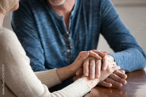 Obraz na płótnie Close up of sensual aged husband and wife holding hands enjoying romantic moment at home, caring senior couple caress and comfort each other, having tender sincere talk