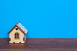Wooden house on the blue background, real estate concept.