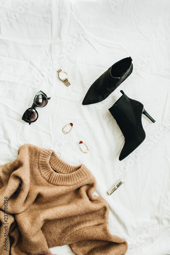 Flat lay, top view fashion concept. Trendy woman clothes and accessories on white blanket. Wall mural