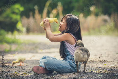 Slika na platnu asia children girl holds a duck in hands