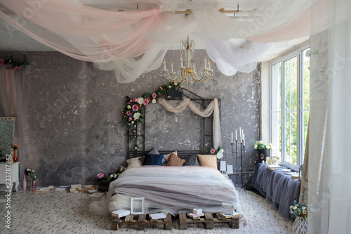 A wood bed in a photo studio decorated with flowers and curtains and sorrounded Slika na platnu