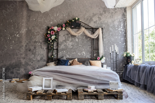 A wood bed in a photo studio decorated with flowers and curtains and sorrounded Fototapeta