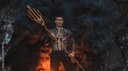 A young man with a trident against the background of fire and smoke Tablou Canvas