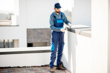 Builder In Uniform Mounting Metal Cover On The Parapet Of A New Building