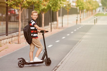 School Boy In Riding With His Electric Scooter In The City With Backpack On Sunny Day. Child In Colorful Clothes Biking On Way To School