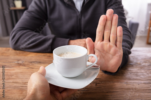 Valokuva  Man Refusing Cup Of Coffee Offered By Person