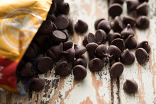 Close Up Of Chocolate Chips On Wooden Table