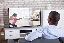 Rear View Of A Man Watching Television