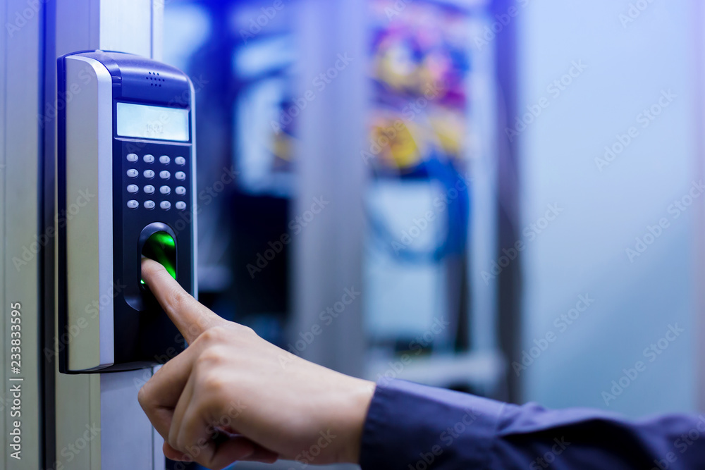 Fototapeta Staff push down electronic control machine with finger scan to access the door of control room or data center.