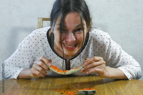 Fotografia, Obraz  Hungry woman quickly eats a watermelon. Eat as a pig.