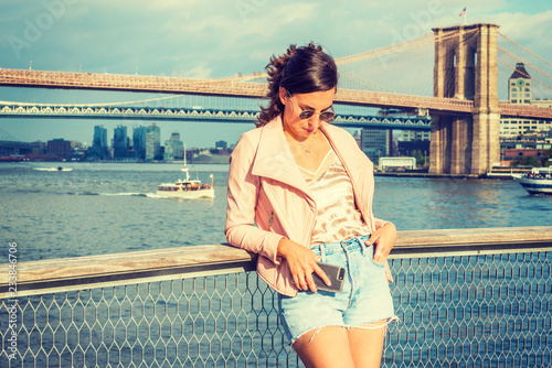 Fotografie, Obraz  Young American Woman traveling in New York, wearing pink leather jacket, blue Denim shorts, sunglasses, standing by river, looking down, thinking