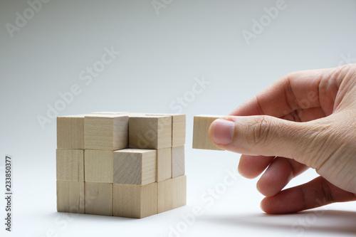 Fotografía  Hand to complete last piece wood cube for a bigger block