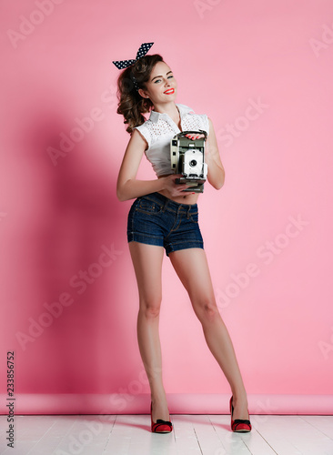 Young pinup style woman take photo use antique old portable photo camera medium Wallpaper Mural