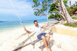 Young attractive happy mix raced man swinging on a swing on the shore of a bright tropical sea, vacations and travel