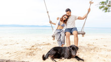 Young Couple Swinging On A Swing On Paradise Tropical Beach With Dog, Honeymoon, Vacation, Travel Concept