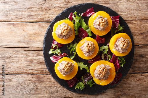 Delicious appetizer peaches stuffed with tuna and decorated with walnuts close-up. horizontal top view