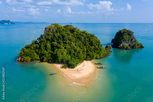 Aerial drone view of an exotic, tiny tropical island with sandy beach and jungle