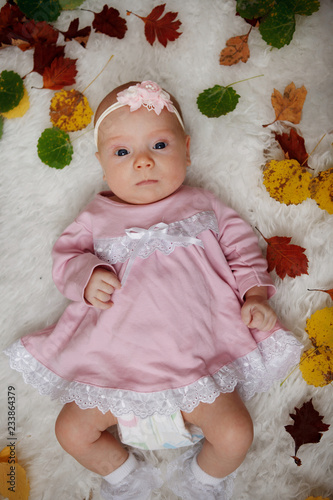 Little cute girl two months old in a pink dress and a flower on her head is lying on a bedspread surrounded by red and yellow autumn leaves.
