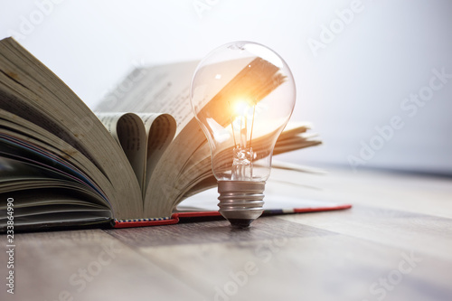 Light bulbs glowing with book Fotobehang