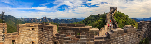 Panoramic view of the Great Wall of China and tourists walking on the wall in the Mutianyu village a remote part of the Great Wall near Beijing