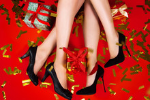 New Year Christmas Winter Party Celebration Concept. Legs Of Females / Women / Girls Tiny Glamour Style Black Shoes On Red Background With Gold  Confetti Presents Gifts Top View
