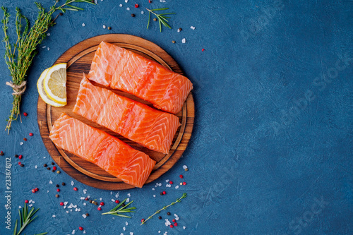Food background, sliced portions large salmon fillet steaks on chopping board on Fototapeta