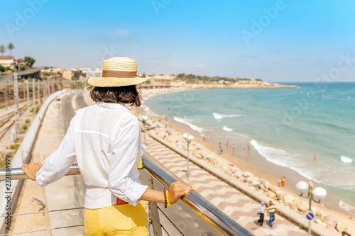 Young woman in hat looking at the beach in Tarragona, Costa Dorada