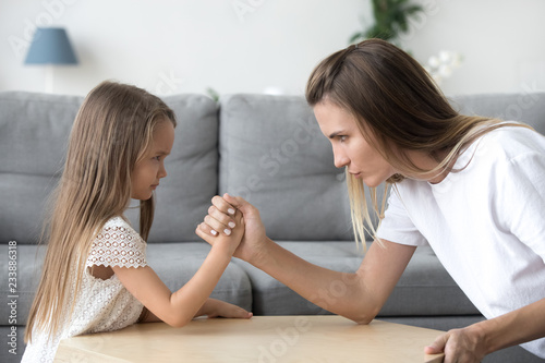 Fotografía  Mom and kid daughter arm wrestling having fight confrontation or family conflict