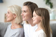 canvas print picture - Smiling beautiful women in three generation family looking forward thinking of bright future, happy grandmother young mother and little child daughter dream of good, growing up, aging process concept
