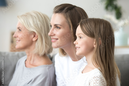 Smiling beautiful women in three generation family looking forward thinking of b Canvas Print