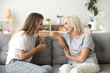 canvas print picture Cheerful old mother and young adult woman talking laughing together, smiling elderly older mum having fun chatting with grown daughter, two age generations pleasant conversation at home concept