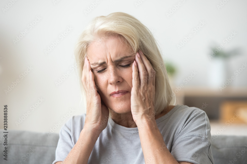 Fototapeta Upset middle aged older woman massaging temples touching aching head feeling strong headache or migraine concept, sad tired stressed elderly senior mature woman suffering from pain or dizziness