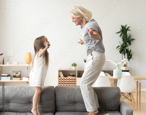 Obraz Cute little girl having fun playing with smiling grandmother jumping on couch together, happy granny and active kid grandchild dancing on sofa, grandma and granddaughter laughing playing at home - fototapety do salonu